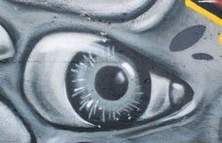 Arte dos grafittis na rua da cidade que mostra o olho pintado na parede cinzenta concreta como o fundo fotografia de stock