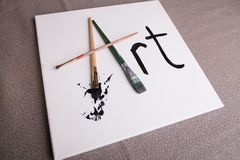 Arte escrita na lona em escovas de pintura e na pintura preta Fotos de Stock