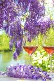 Arte francese di vivere: due vetri di vino rosato e della viola da gamba di fioritura Immagini Stock