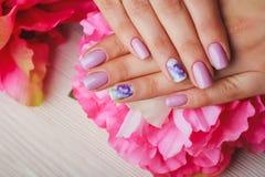 Arte lilás do prego com as flores impressas no fundo claro Fotografia de Stock Royalty Free