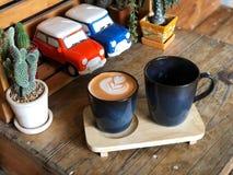 Arte tailandesa do latte do chá e bebida quente no copo preto na bandeja de madeira fotografia de stock royalty free