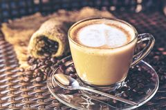 Arte y capuchino del latte de la taza de café con en forma de corazón hecha de la leche en la tabla de madera con los granos de c foto de archivo libre de regalías