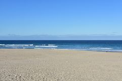 Beach with golden sand and blue sea with small waves with foam. Clear sky, sunny day. Arteijo, Galicia, Spain. Arteijo, La Coruna Province, Galicia, Rias Altas royalty free stock photos