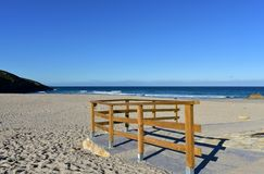 Beach with wooden handrail and morning light. Golden sand and blue sea with waves and white foam. Sunny day, Galicia, Spain. Arteijo, La Coruna province stock photography
