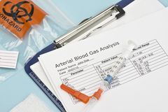 Arterial Blood Gas Syringe. Arterial blood gas sample syringe on sterile drape with laboratory report. Heparin is a common non-trademarked medication name stock photography