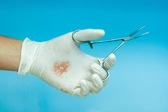 Artery Forceps. In hands stained with blood royalty free stock photos