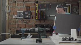 Artes?o profissional que trabalha com as ferramentas na garagem O conceito da fabrica??o da m?o, Craftman trabalha em uma oficina video estoque