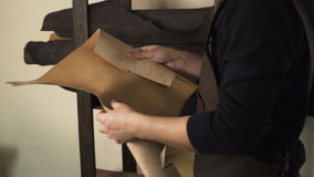 Artesão que inspeciona uma parte de couro filme