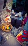 Artesão que trabalha lãs naturais, em um quadrado em Rovereto sob festivais do Natal, criando scarves e mais para a venda imagens de stock