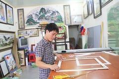 Artesão que trabalha no quadro na loja do quadro Fotos de Stock Royalty Free