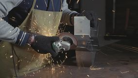 Artesão que usa um moedor de ângulo para o detalhe polonês do metal na oficina filme