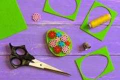 Artes del huevo de Pascua del fieltro La decoración del huevo de Pascua del fieltro con la flor de madera colorida abotona Pedazo Imagen de archivo