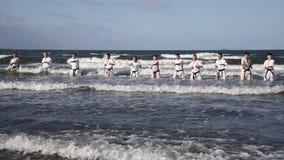 Artes marciales del karate japonés que entrenan en la playa metrajes