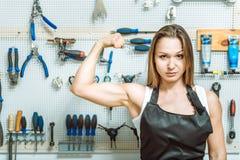 Artesana dominante que demuestra su bíceps en el taller fotografía de archivo