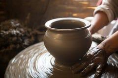 artesanía Primer de las manos que trabajan la arcilla en la rueda de alfarero Fotos de archivo
