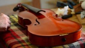Artesano de Luthier que trabaja en un violín o una viola en lugar de trabajo almacen de metraje de vídeo