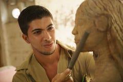 Artesano joven del artista del escultor que trabaja esculpiendo la escultura Foto de archivo