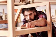 Artesano que enarena un artículo de madera en su estudio de la artesanía en madera imagen de archivo