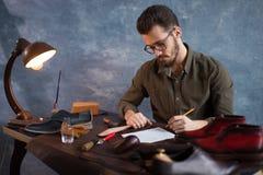 Artesano que escribe un bosquejo de las botas imagen de archivo libre de regalías