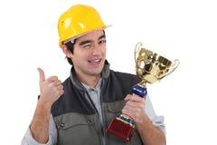 Artesano que guiña sosteniendo el trofeo Imágenes de archivo libres de regalías