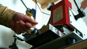 Artesano que trabaja con la prensa del sello de la libra Impresión del sello en el material de cuero metrajes