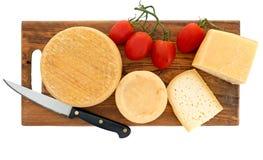 Artesano, queso de la granja a bordo con los tomates rojos y cuchillo Fotografía de archivo