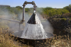 Artesian water supply. Artesian water coming straight from the ground being put into channels to cool it for use Stock Photo