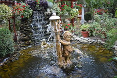 Artesian well with statues small waterfall and flowers  . Royalty Free Stock Image