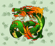 Artful green Asian dragon against leaves. Artful green and red wood Asian dragon or Celtic dragon against green leaves Royalty Free Stock Photography