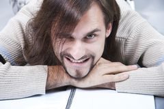 Artful young man lies on a writing-book Royalty Free Stock Images