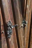 Artfully executed metal door handle. Photo taken in Bratislava. On the photo, an artfully made door handle on an old wooden door Royalty Free Stock Photo