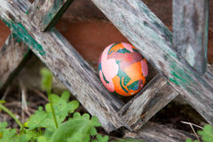 Artfully Painted Easter Egg. An Easter egg hidden among a wood truss Royalty Free Stock Image