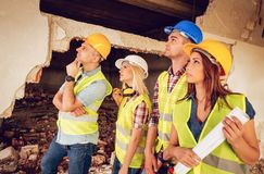 Arthitects Planing Reconstruction. Four construction architects review building damaged in the disaster Royalty Free Stock Photography