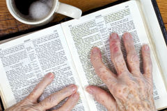 Arthritic Hands & The Ancient Word. Elderly woman's arthritic hands holding her hebrew language bible as she reads from Isaiah 53 Royalty Free Stock Photos