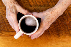 Arthritic Hands & Coffee Cup. Elderly woman's arthritic hands holding a cup of black coffee Royalty Free Stock Photography