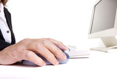 Arthritic worker. Older senior business woman's arthritic hand with knobbly finger operating mouse Royalty Free Stock Images