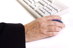 Arthritic worker. Older senior business woman's arthritic hand with knobbly finger operating mouse Stock Photos