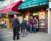 Arthur Ave. The Bronx. BRONX, NEW YORK CITY - DEC 28: People waiting on line outside traditional Italian cheese market on Arthur Avenue in the Bronx on December stock image