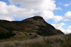 Arthur's Seat In Edinburgh with Puffy White Clouds Stock Images
