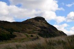 Arthur& x27; s Seat W Edynburg z Bufiastymi Białymi chmurami Obrazy Stock