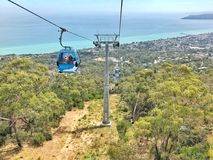 Arthurs Seat Eagle chairlift. People having a ride on the Arthurs Seat gondola or chair lift overlooking seascape and township which is situated on the Stock Photo
