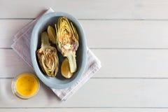 Artichauts et citrons du plat Fond en bois blanc Ce produit a une des capacités antioxydantes les plus élevées Images stock