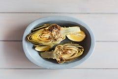 Artichauts et citrons du plat Fond en bois blanc Ce produit a une des capacités antioxydantes les plus élevées Photos stock