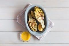Artichauts et citrons du plat Servi avec de la sauce Fond en bois blanc Ce produit a un du plus haut Photographie stock libre de droits