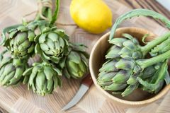 Artichoke bouquets on kitchen table. Two artichoke bouquets on kitchen table among some kitchen items. Top view royalty free stock photos