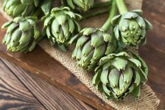 Artichoke bouquets on sackcloth on wooden background. Two artichoke bouquets on kitchen table among some kitchen items. Top view royalty free stock image