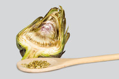 Artichoke cut in half and wooden spoon with fennel seeds Stock Photography