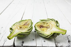 Artichoke cut in half on wooden white table Stock Photo