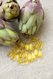 Artichoke oil in the capsules. Capsules with artichoke oil on a sackcloth Stock Images
