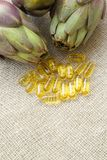 Artichoke oil capsules. Capsules with artichoke oil on a sackcloth. Free space for a text Stock Photography